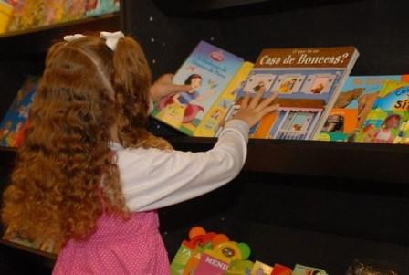 Menina olha livro infantil na livraria da CAASP
