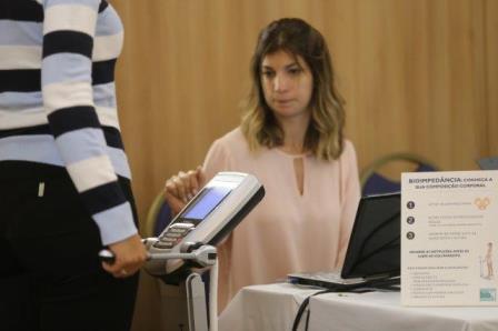 Mulher realiza exame de massa corporal