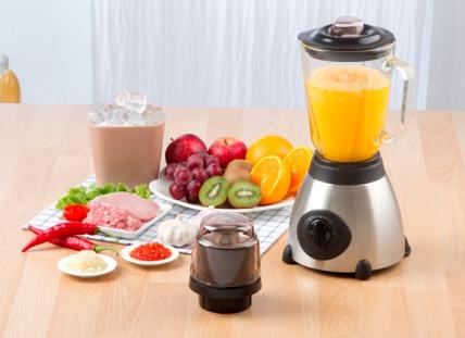 Liquidificador em mesa com prato de frutas