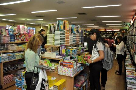 Pessoas folheiam livros infantis na livraria da CAASP